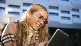 Sluit omhoog geschoten van leuk glimlachend meisje in zonnebril gebruikend tablet voor het babbelen met iemand op de buiding acht stock videobeelden