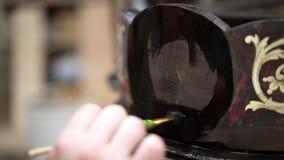Sluit omhoog geschoten van mannelijke hand die antieke kast refinishing gebruikend zwarte verf stock video