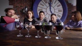 Sluit omhoog geschoten van meer sommelier wie een rode wijn op een glas voor een bedrijf van vrienden giet dat op de achtergrond  stock videobeelden