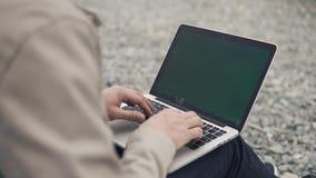 Sluit omhoog geschoten van mensen` s handen die in openlucht aan laptop onder een rotsachtig strand werken stock videobeelden