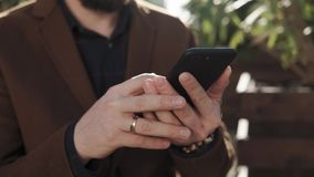 Sluit omhoog geschoten van mensen` s handen die tekst sms op een mobiele telefoon drukt stock videobeelden