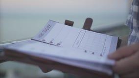 Sluit omhoog geschoten van mensenhand het flicking door pagina's van de het notitieboekjeagenda van de dagboek de dagelijkse ontw stock video