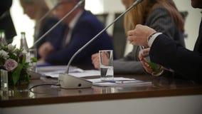 Sluit omhoog geschoten van mensenhanden tijdens bespreking op de conferentievergadering Flessen water en glazen op de lijsten stock footage