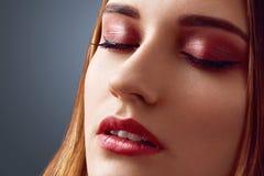 Sluit omhoog geschoten van mooi wijfje met gezonde zuivere huid, houdt ogen gesloten, aantoont aardig omhoog maak, geïsoleerd ove stock afbeeldingen