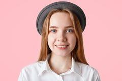 Sluit omhoog geschoten van tevreden gelukkige tiener stelt voor populair maniertijdschrift, draagt in hoed en het elegante witte  royalty-vrije stock foto's