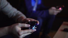 Sluit omhoog geschoten van twee jonge mensen drukt snel de knopen op spelconsoles stock footage