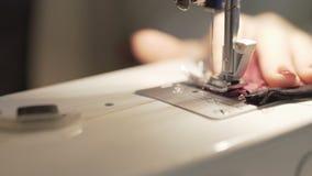 Sluit omhoog geschoten van vrouwelijke handen die aan naaimachine werken De jonge ontwerper die van het vrouwenconcept aan een na stock videobeelden