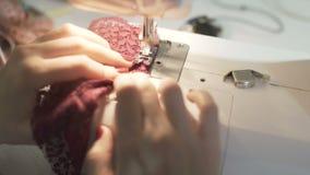 Sluit omhoog geschoten van vrouwelijke handen die aan naaimachine werken De jonge ontwerper die van het vrouwenconcept aan een na stock footage