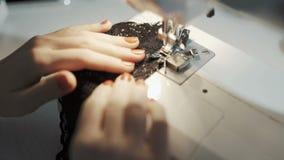 Sluit omhoog geschoten van vrouwelijke handen die aan naaimachine werken De jonge ontwerper die van het vrouwenconcept aan een na stock video