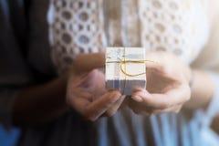 Sluit omhoog geschoten van vrouwelijke handen houdend een kleine gift Stock Afbeeldingen