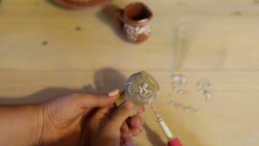 Sluit omhoog geschoten van weinig jongen het schilderen klei ceramische pot op de workshop van de aardewerkkunst voor jonge geitj stock video