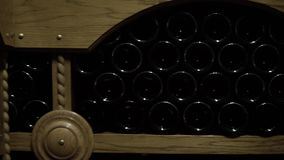 Sluit omhoog geschoten van Wijnflessen liggend in stapel bij kelder Glasflessen rode die wijn in het houten opschorten in steen w stock footage