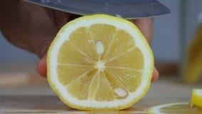 Sluit omhoog geschotene handen van vrouw gebruikend de gesneden verse citroen van het keukenmes plak stock video