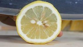 Sluit omhoog geschotene handen van vrouw gebruikend de gesneden verse citroen van het keukenmes plak stock videobeelden