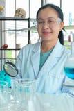 Sluit omhoog geschotene, midden-Leeftijds Aziatische vrouwelijke wetenschappers, die glazen en hand houdend een vergrootglas drag royalty-vrije stock fotografie