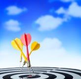 Sluit omhoog geschotene rode pijltjepijl op centrum van dartboard en gele a Stock Afbeeldingen