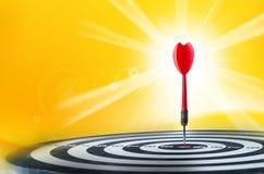 Sluit omhoog geschotene rode pijltjepijl op centrum van dartboard, metafoor aan Stock Fotografie