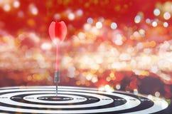 Sluit omhoog geschotene rode pijltjepijl op centrum van dartboard op bokehblu Royalty-vrije Stock Foto