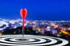 Sluit omhoog geschotene rode pijltjepijl op centrum van dartboard op stad en Stock Foto's