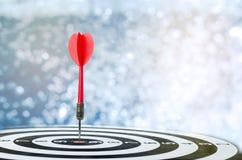 Sluit omhoog geschotene rode pijltjepijl op centrum van dartboard over bokeh B Royalty-vrije Stock Foto's