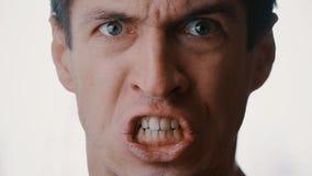 Sluit omhoog gezicht van een jonge mensen boze mens die met woede en bedreigd geweld gillen stock video