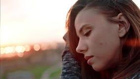 Sluit omhoog gezicht van jonge peinzende vrouw die melancholically naar verbazende zonsondergang en wat betreft haar kijken stock footage