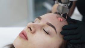 Sluit omhoog gezicht van jonge vrouw bij de behandeling van het lasergezicht in kliniek, langzame motie stock videobeelden