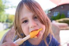 Sluit omhoog gezicht van meisje het kijken en het bijten van oranje ijslollie royalty-vrije stock foto's