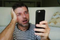 Sluit omhoog gezichtsportret van de jonge aantrekkelijke en beklemtoonde mens gebruikend mobiele die telefoon in gefrustreerd wor royalty-vrije stock foto