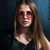 Sluit omhoog gezichtsportret van mooie Kaukasische jonge vrouw met los haar in het modieuze roze ronde zonnebril kijken Stock Foto