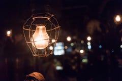 Sluit omhoog gloeilamp met kabels in donkere plaats Retro stijl met bokeh Stock Foto