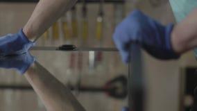 Sluit omhoog gloved hand van de timmerman die op de spiegeloppervlakte drukken, het lijmen aan de raad Concept hand stock footage