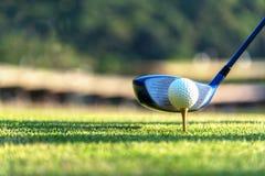 Sluit omhoog golfbal en bestuurder, speler die het T-stuk van de golfschommeling weg op de groene tijd van de zonsondergangavond  stock foto