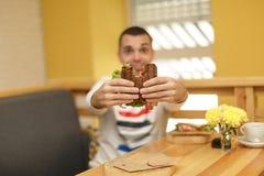 Sluit omhoog grappig vaag protrait van jonge mensengreep gebeten sandwich door zijn twee handen Sandwich in nadruk Lichte achterg stock afbeelding