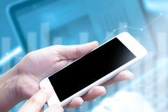 Sluit omhoog hand gebruikend mobiele telefoon met lege vertoning op laptop en grafiek vage achtergrond Het concept is technologie Royalty-vrije Stock Afbeeldingen