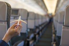 Sluit omhoog hand houdend een vliegtuigmodel binnen een groot vliegtuig Stock Foto's