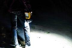 Sluit omhoog hand houdend elektrisch toortsflitslicht in donkere aard bos openlucht status op zand a stock afbeeldingen