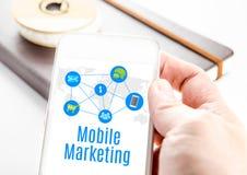 Sluit omhoog hand houdend slimme telefoon met Mobiel marketing woord en Royalty-vrije Stock Fotografie