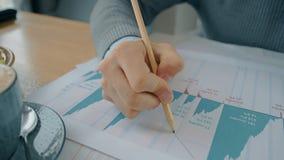 Sluit omhoog hand van de markttendensen van de zakenmantekening op grafieken tijdens lunch in koffie stock video