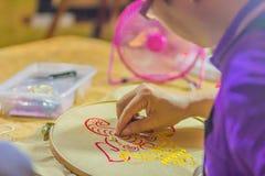 Sluit omhoog hand van de mens terwijl borduurwerk thuis met hoepel en naald Het borduurwerk is de ambacht van het verfraaien van  royalty-vrije stock fotografie