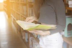 Sluit omhoog hand van het sexy jonge meisje die van Asain een boek en een standi houden Stock Afbeelding