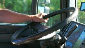 Sluit omhoog hand van mannelijk bestuurdersholding stuurwiel en het drijven van zijn vrachtwagen bij de landweg Mens die zijn vra stock footage