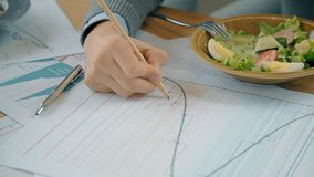 Sluit omhoog hand van mannelijke financiële analitische tekeningstendensen op document grafieken in de koffie stock video