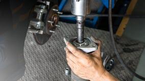 Sluit omhoog hand van mechanische mensen seting schok op absorptievat voor de dienst van de autoopschorting in autogarage en exem stock foto's