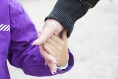 Sluit omhoog hand van moederholding en leid haar kind in wintertijd, zorgconcept stock foto