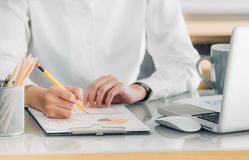 Sluit omhoog hand van onderneemsterhand schrijvend een rapport vooraan o stock afbeelding
