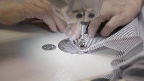 Sluit omhoog handbediend schot van volwassen vrouwelijke handen die kant van gestreepte stof naaien stock video