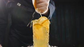 Sluit omhoog handchef-kok die sinaasappel op vers fruitcocktail drukken in langzame motie sap die uit fruit druppelen Binnen het  stock video