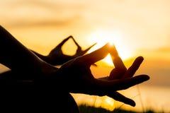 Sluit omhoog handen De vrouw doet yoga openlucht Vrouw essentieel uitoefenen en meditatie voor geschiktheidslevensstijl op de ach stock afbeelding