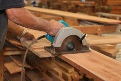Sluit omhoog handen van hogere timmerman die een stuk van hout snijden tegen elektrische cirkelzaag in timmerwerk woodshop Houtbe Stock Foto